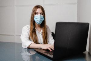 Frau mit Mund-Nase-Schutz an Laptop